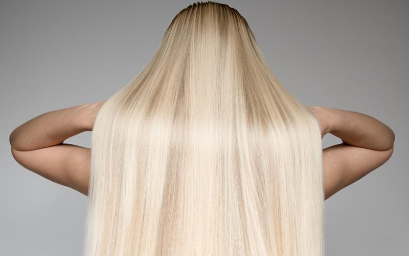 Frau mit blondem glatten Haar von hinten
